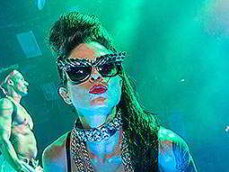 A woman wearing sunglasses and a chain necklace, pouting at the camera
