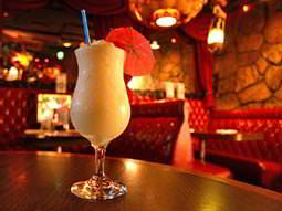 Creamy cocktail in bar with red leather booths