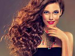 A made up woman with red lipstick and nails, and long wavy hair