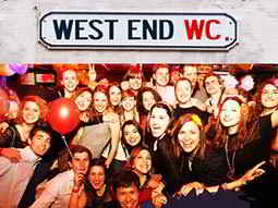 A group photograph of men and women on a night out, with a West End street sign above them