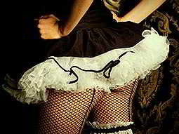 The body of a woman wearing a short, tutu-style skirt and black fishnet leggings