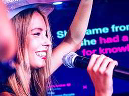 A woman in a hat singing into a mic, with song lyrics on a TV in the background