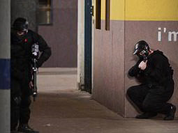 A man hiding behind a wall in black overalls whilst holding an airsoft gun, and a man crouching behind a wall