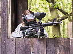 A person leaning over a fence, aiming a paintball gun
