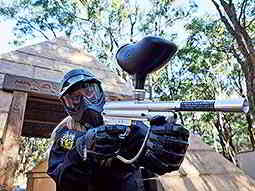A close up of a woman wearing paintball mask and overalls aiming a silver paintball marker