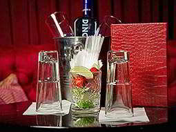 Cocktail ingredients a bottle of spirits in an ice bucket and two glasses on a table, in a booth