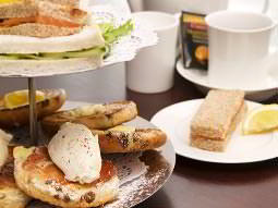 An afternoon tea platter laid out with sandwiches, teacakes, scones and cups of tea