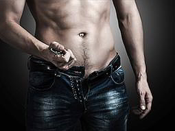 A close up of a naked male torso and jeans, with the zip open