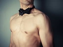 A close up of a naked male torso and black bowtie