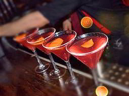 A line of four red cocktails on a bar, with an orange in each glass