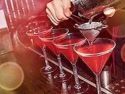 Line of four red cocktails with a hand holding a strainer above one of the cocktails