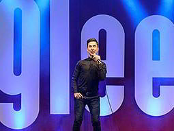 A man with a microphone in front of a large 'Glee' logo