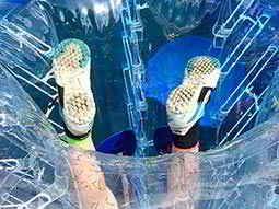 Close up of a mans trainers peeking out of an upside down inflatable zorb