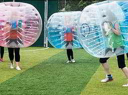 People playing bubble football in red and blue inflatable bubbles