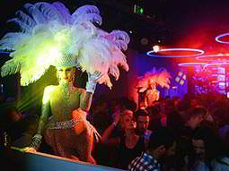 A woman wearing a cabaret-style feather headdress with a busy room in the background