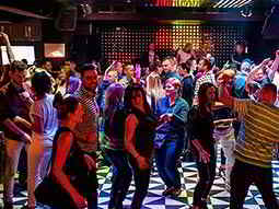 A group of people dancing on a chequered-patterned dance floor