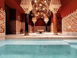 An indoor pool with large indoor columns in the background, in an Arabian Baths