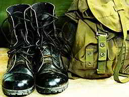 Black army boots next to a green rucksack