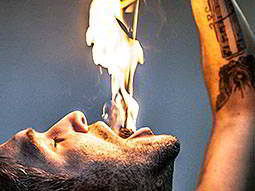 A man holding a flaming stick down his throat