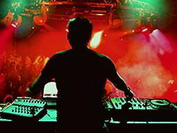 A DJ performing to a crowd of people under red and green lights