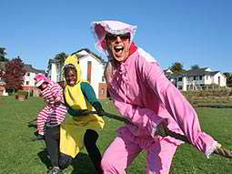 Three women dressed up in costumes doing tug of war