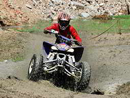 A man driving a quad bike through mud