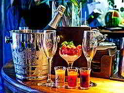 An ice bucket containing a bottle of champagne next to a glass of fruit, two champagne flutes and shot glasses of fruit puree