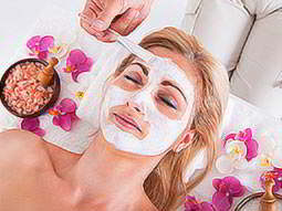 A woman receiving a facial with a white face mask, on a bed of flowers