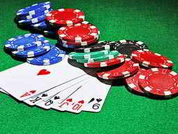 Six playing cards and various casino chips lying on a green felt surface