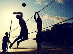 Silhouette of men playing beach volleyball