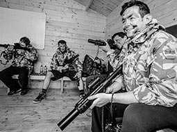 Black and white image of men sat down in military jackets, whilst holding laser guns
