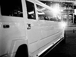 Black and white, close up image of a white hummer limo, parked up