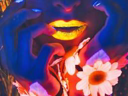 Close up of a woman touching her lips and face under UV light and with UV lipstick on
