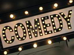 comedy sign lit up in stage lights