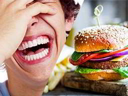 big mouth laughing, split with colourful burger served on a wooden board