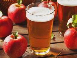Pint of cider alongside red apples