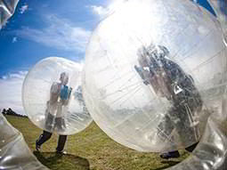 Two people about to collide whilst playing Bubble Football