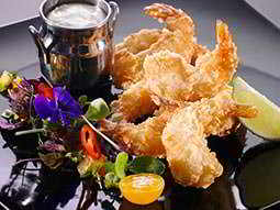 A plate of battered prawns and salad with a metal pot of sauce
