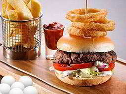 A board with chips, sauce and a burger (topped with onion rings) on