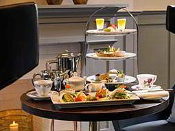 A table set of afternoon tea with a cake stand, teapot and cups and a plate of food
