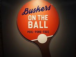 The table-tennis-bat-shaped logo of Buskers on the Ball