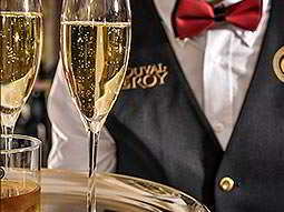 Two glasses of champagne with a man in a waistcoat standing behind