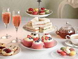 An afternoon tea set up with cakes on plate and pink champagne