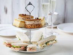 Finger sandwiches and dainty treats on a high tea stand