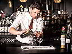 Close up of a bartender in a white shirt, pouring out two cocktails through a sieve and into a martini glass