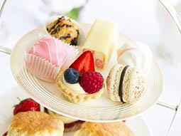 The top level of a cake stand, filled with small cakes and pastries