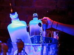 An ice bucket with bottles of vodka in being filled up from a soda tap