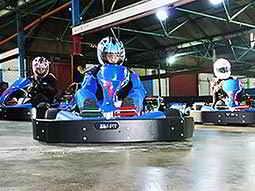 Three go karts racing on an indoor circuit