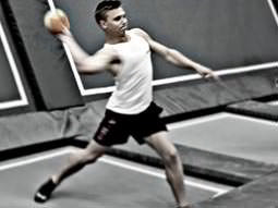 A man preparing to throw an orange ball