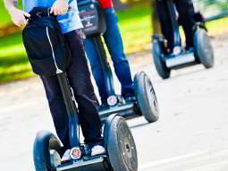 Line of three peoples legs riding Segways